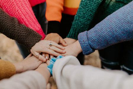 Groupe de personnes aux manches multicolores joignant leurs mains