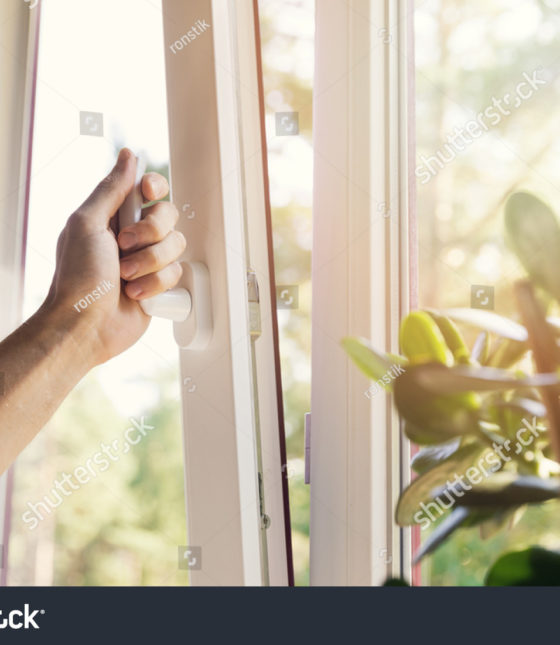 stock-photo-hand-open-white-plastic-pvc-window-at-home-694361635